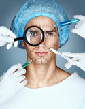 Portrait of male in medical headwear while four hands in medical gloves holding syringes and knifes close to his face royalty free stock images