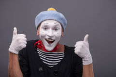 Portrait of male mime white funny face and. Waist-up portrait of funny male mime with grey hat and white face showing sign OK with both hands and looking at the Royalty Free Stock Image