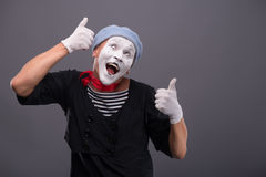 Portrait of male mime white funny face and. Waist-up portrait of funny male mime with grey hat and white face showing sign OK with both hands and looking Royalty Free Stock Photo