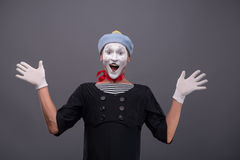 Portrait of male mime white funny face and. Waist-up portrait of funny male mime with grey hat and white face smiling looking at the camera with great surprise royalty free stock photo