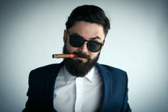 Portrait of male model making angry face and smoking a cigar Royalty Free Stock Image