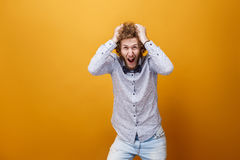 Depressed hysterical young man screaming against of yellow backg Stock Photo