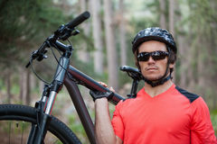 Portrait of male mountain biker carrying bicycle in the forest Stock Photo