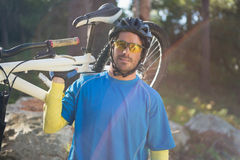 Portrait of male mountain biker carrying bicycle in the forest Stock Photography