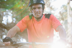 Portrait of male mountain biker riding bicycle in the forest Royalty Free Stock Photography