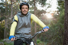 Portrait of male mountain biker riding bicycle in the forest Royalty Free Stock Image