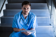 Portrait of male nurse sitting on staircase and using digital tablet. Of hospital Royalty Free Stock Photo