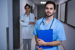 Portrait of male nurse standing with doctor in background. At hospital corridor Stock Photography