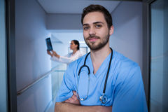 Portrait of male nurse standing with doctor in background. At hospital corridor Stock Photos