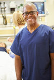 Portrait Of Male Nurse Working In Emergency Room. Wearing Scrubs Smiling To Camera With Nurse And Patient In Background Stock Photos