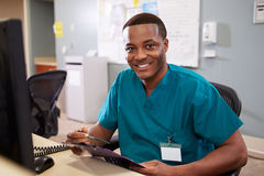 Portrait Of Male Nurse Working At Nurses Station Stock Image