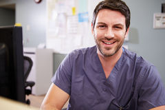Portrait Of Male Nurse Working At Nurses Station. Wearing Scrubs Smiling To Camera Royalty Free Stock Photo