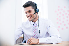 Portrait of a male operator with headset. Using PC in office Royalty Free Stock Photo