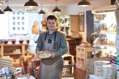 Portrait Of Smiling Male Owner Of Delicatessen Shop Wearing Apron Holding Loaf Of Bread stock images