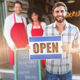 Composite image of portrait of male owner holding open sign Royalty Free Stock Photography