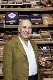 Portrait of a male owner of tobacco shop standing with cigar boxes in background Stock Images