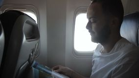 Portrait of male passenger, who is reading magazine in the modern aircraft. Man in white t-shirt and with beard is sitting on comfortable seat, near the window stock video footage