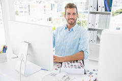 Portrait of a male photo editor working on computer. In a bright office Stock Photos