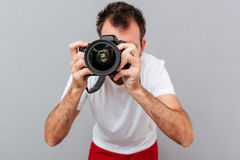 Portrait of a male photographer with camera taking photo Stock Image