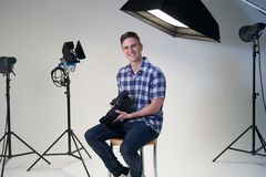 Portrait Of Male Photographer In Studio For Photo Shoot With Camera And Lighting Equipment. Portrait Of Male Photographer In Studio For Photo Shoot With Camera stock photography