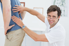 Portrait of a male physiotherapist examining mans back Royalty Free Stock Image