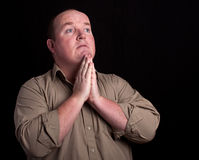 Portrait of male praying on black background Stock Photography