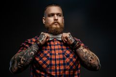 Portrait of male in red shirt and grey bow tie. Portrait of male in red shirt and grey bow tie with tattoes on his hands. Isolated on black Royalty Free Stock Photos