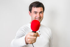 Portrait of male reporter with red microphone. Journalism and broadcasting concept Royalty Free Stock Images