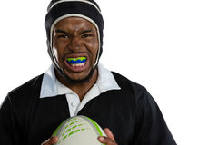 Portrait of male rugby player wearing mouthguard white holding rugby ball. Against white background Royalty Free Stock Photography