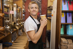 Portrait of male salesperson holding disposable coffee cup in store Stock Image