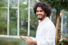 Portrait of male scientist using digital tablet. Portrait of happy male scientist using digital tablet outside greenhouse Royalty Free Stock Image