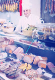 Portrait of male seller posing with wursts in butchery. Portrait of positive european male seller posing with wursts in butchery Royalty Free Stock Photo