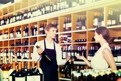 Portrait of male seller  showing bottle of wine to female custom. Portrait of happy european male seller in uniform showing bottle of wine to female customer in Stock Image