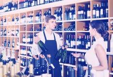 Portrait of male seller  showing bottle of wine to female custom. Portrait of happy russian male seller in uniform showing bottle of wine to female customer in Stock Photos