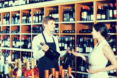 Portrait of male seller  showing bottle of wine to female custom. Portrait of happy spanish male seller in uniform showing bottle of wine to female customer in Royalty Free Stock Photos