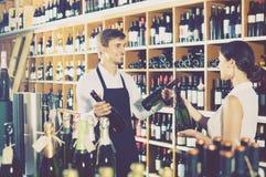 Portrait of male seller  showing bottle of wine to female custom. Portrait of happy male seller in uniform showing bottle of wine to female customer in wine shop Stock Photos