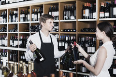 Portrait of male seller  showing bottle of wine to female custom. Portrait of smiling male seller in uniform showing bottle of wine to female customer in wine Royalty Free Stock Photography