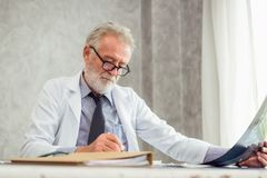 Portrait of male senior doctor is examining X-Ray film in examination room, Healthcare and occupational concept. Portrait of male senior doctor is examining X royalty free stock images