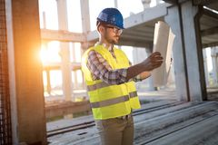 Portrait of male site contractor engineer with hard hat holding blue print paper Stock Photo