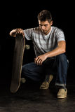 Portrait of a male skater holding a skateboard and looking at the camera. While kneeling down, isolated on black background Royalty Free Stock Images