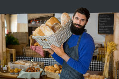 Portrait of male staff carrying wicker basket of breads at counter. In bakery shop Royalty Free Stock Photo