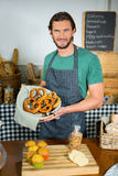 Portrait of male staff holding basket of pretzel at counter. In bakery shop Stock Photos