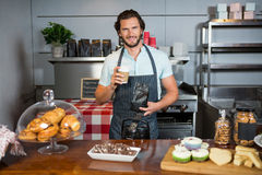 Portrait of male staff holding coffee cup and coffee bag at counter. In coffee shop Royalty Free Stock Images