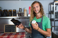 Portrait of male staff holding coffee cup and parcel bag at counter. In coffee shop Royalty Free Stock Photography