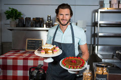 Portrait of male staff holding dessert on cake stand at counter Royalty Free Stock Photo