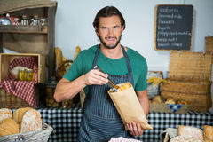Portrait of male staff packing bread in paper bag. In bakery shop Stock Photo