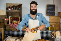 Portrait of male staff packing pretzel in paper bag. In market Royalty Free Stock Photo