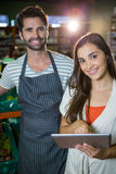 Portrait of male staff standing with a woman using digital tablet. Portrait of male staff standing with a women using digital tablet in supermarket Stock Photography