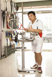 Portrait of a male staff in tennis shop. A male staff is very confidently with a racket in hand Royalty Free Stock Photo