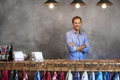 Portrait Of Male Store Owner Standing Behind Cash Desk royalty free stock image